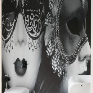 W tej łazience dla gości wyposażenie ograniczono do minimum, zaś główną rolę gra tutaj fototapeta z kobiecą twarzą w weneckiej masce, która stanowi niecodzienną dekorację. Projekt: Katarzyna Mikulska Sękalska. Fot. Bartosz Jarosz.