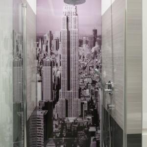 Ścianę przy prysznicu ozdobiono fototapetą, którą następnie zabezpieczono szkłem. Wysoki budynek górujący nad resztą miasta może budzić metaforyczne skojarzenia ze smukłym kształtem ludzkiego ciała. Projekt: Anna Maria Sokołowska. Fot. Bartosz Jarosz.