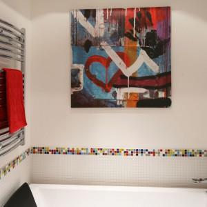 W tej łazience mozaikę nad wanną wykończono kolorową bordiurą inspirowaną kostką Rubika. To właśnie do niej dopasowany jest barwny obraz, przywodzący na myśl uliczne graffiti. Projekt: Dorota Szafrańska. Fot. Bartosz Jarosz.