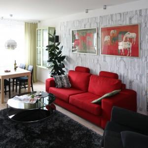 W niedużym salonie jadalnię organizuje mały stolik pomyślany na cztery osoby. Ustawiony tuż za nim czerwona sofą subtelnie wtapia się w tło. Projekt: Marta Kruk. Fot. Bartosz Jarosz.