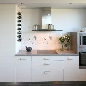 Fronty mebli w tej kuchni są białe, matowe i albo całkowicie gładkie, albo zwieńczone przez prostokątne, płaskie uchwyty również w białym kolorze i - co ciekawe - także matowe. Tak wykończone meble harmonizują z białą ścianą nie tylko kolorem, ale i fakturą. Całość przełamano szkłem nad blatem, z delikatnymi, dekoracyjnymi kwiatuszkami. Projekt: Arkadiusz Grzędzicki. Fot. Bartosz Jarosz.