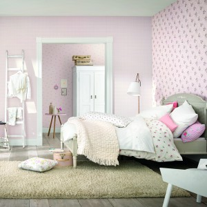 Różowa tapeta w drobne kwiatki z serii Lazy Sunday niemieckiej marki Rash wprowadzi do sypialni klimat sprzyjający przyjemnemu relaksowi. Tapetą można ozdobić wszystkie ściany lub tylko jedną z nich. Fot. Rash.