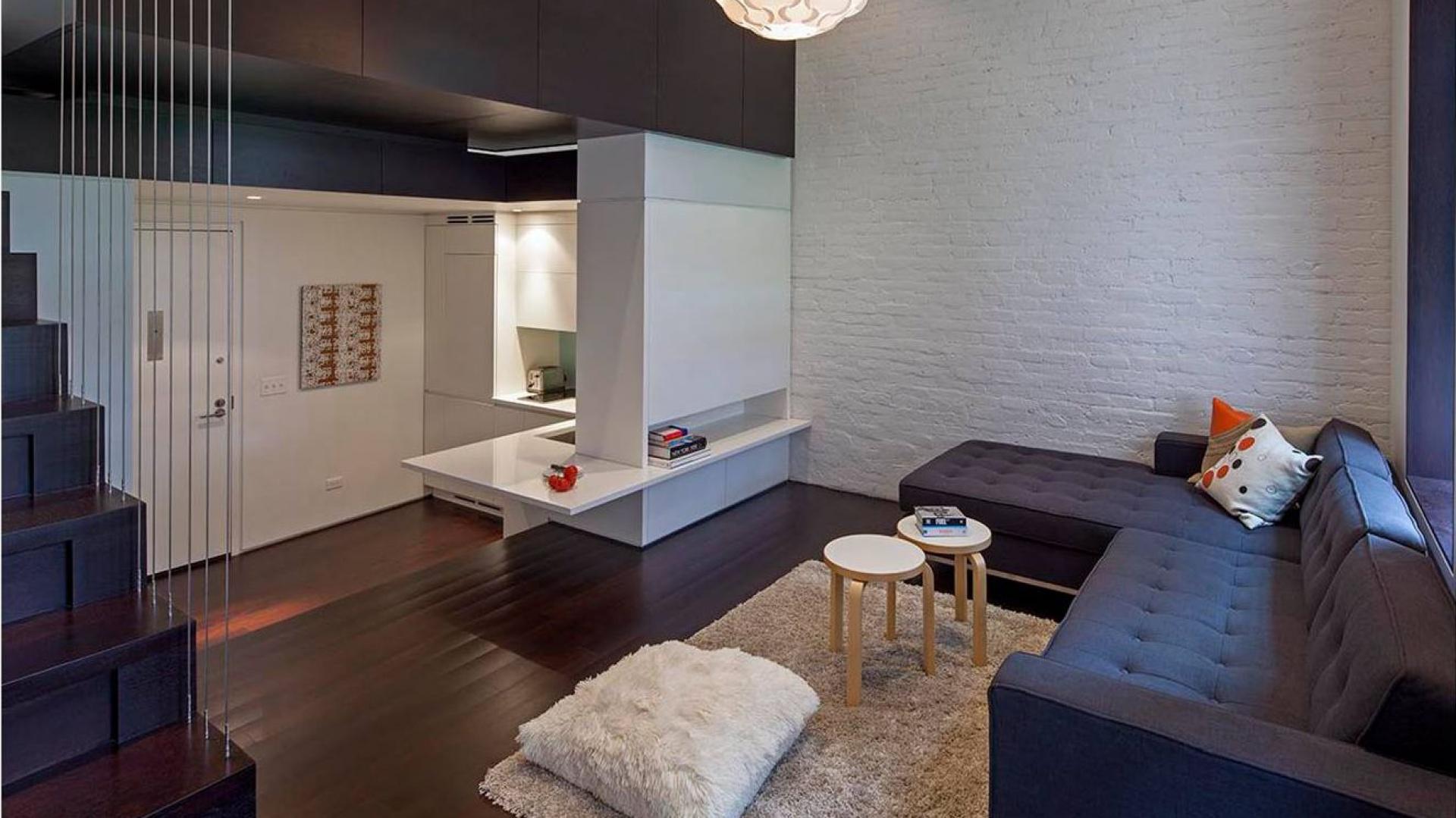 Na drugim poziomie urządzono niewielki salon z bezpośrednim widokiem na mini-kuchnię i wejście do mieszkania. Mimo ograniczonej przestrzeni udało się tutaj wpasować całkiem spory narożnik, przytulny dywan i poduchę-siedzisko. Projekt: Specht Harpman. Fot. Zdjęcia: Taggart Sorenson.