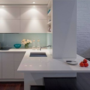 Blat kuchenny zyskał dodatkową powierzchnię dzięki poprowadzeniu go wzdłuż drugiej niewielkiej ściany, zamykającej symbolicznie pomieszczenie oraz wypuszczenie go delikatnie w przestrzeń schodów, prowadzących na drugi poziom mieszkania. Projekt: Specht Harpman. Fot. Zdjęcia: Taggart Sorenson.