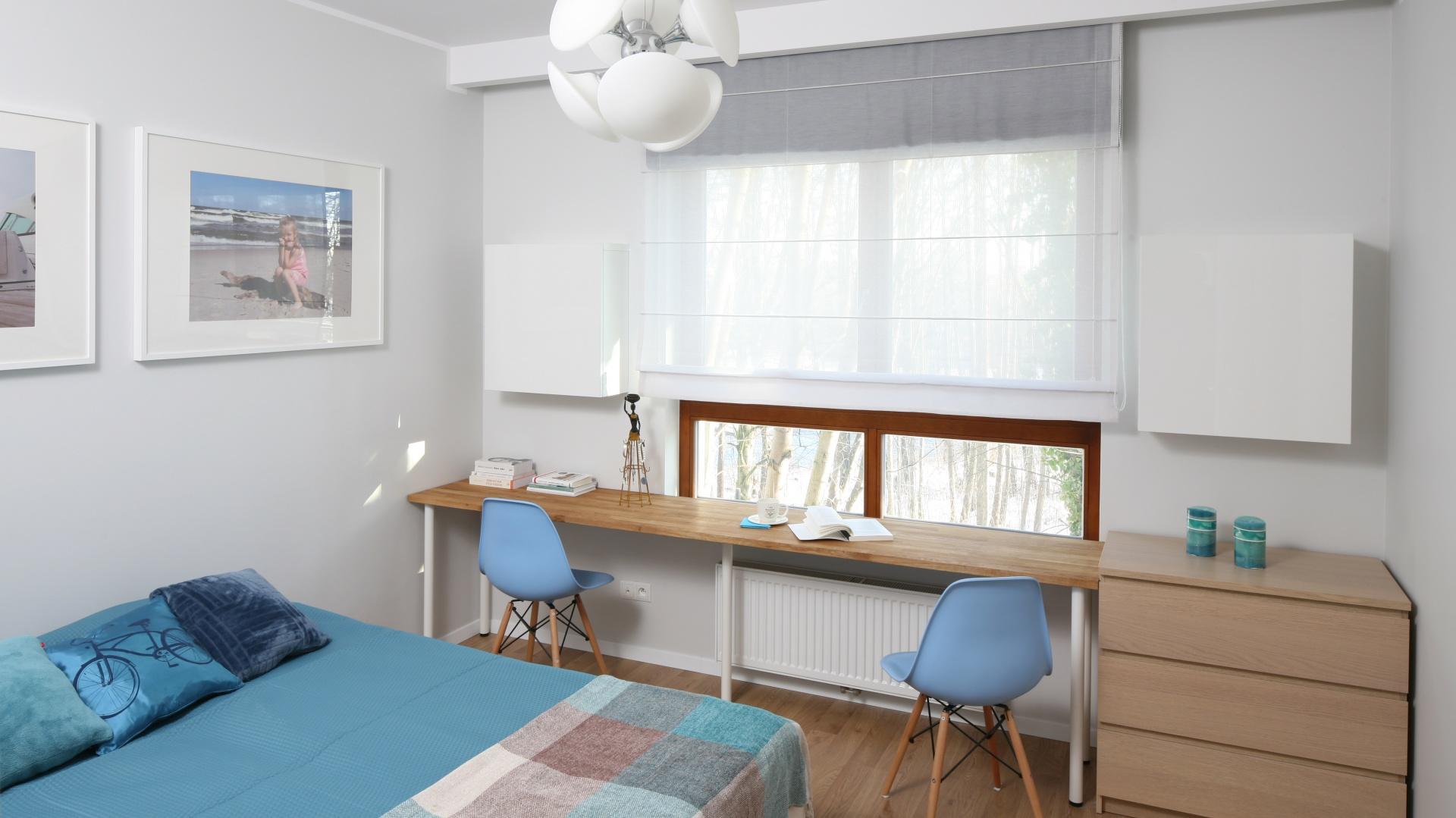 Białą sypialnię ocieploną drewnem wzbogacono o niebieskie dodatki, dzięki czemu powstała aranżacja w kolorze nadmorskiej plaży. Krzesła z błękitnymi siedziskami, ustawione przy długim blacie biurka, nadają strefie pracy gustowny, lekki wygląd. Projekt: Anna Maria Sokołowska. Fot. Bartosz Jarosz.