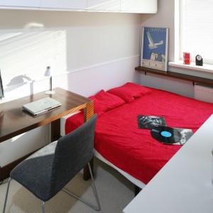 Ta sypialni jest przykładem, że nawet na bardzo małej przestrzeni można zorganizować miejsce do pracy. Niewielkie drewniane biurko ustawiono w rogu, bezpośrednio przy łóżku. Projekt: Marcin Lewandowicz. Fot. Bartosz Jarosz.