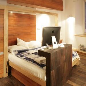 Najciekawszym elementem sypialni z drewna jest niska ścianka wyłaniająca się z płaszczyzny podłogi, na której ustawiono telewizor. Projekt: Michał Swałtek. Fot. Bartosz Jarosz.
