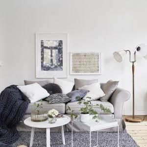 Przytulność w przestrzeni dziennej budują dekoracyjne tekstylia. Ich mnogość ociepla wnętrze, jednak kolorystyka jest stonowana i dość chłodna, przez co nie zaburzają one eleganckiej aranżacji. Fot. Jonas Berg/Stadshem.