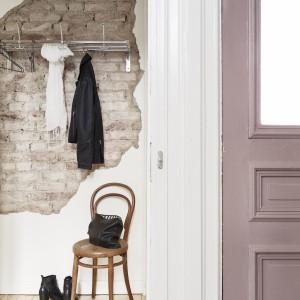 Odważny element dekoracyjny wnętrza: miejsce na powieszenie ubrania zostało dodatkowo wyeksponowane poprzez ścianę, na której zamontowano wieszak. Odsłonięta czerwona cegła z nieregularnymi krawędziami powierzchni tworzy ciekawy efekt wizualny. Fot. Jonas Berg/Stadshem.