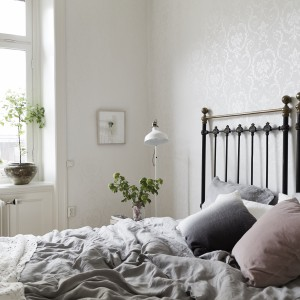 Ściany w kolorze złamanej bieli zdobi tapeta z bardzo subtelnym kwiecistym wzorem, widocznym dzięki załamującemu się na powierzchni ściany świetle. Tworzy on bardzo delikatną i romantyczną dekorację. Fot. Jonas Berg/Stadshem.