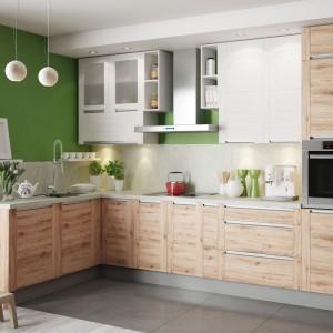 Kuchnia Olivia Soft w pięknej, jasnej wersji kolorystycznej. Ciepła barwa drewna wprowadza przytulną atmosferę do przestrzeni kuchni i wspaniale harmonizuje z zielenią na ścianie, z którą wspólnie tworzy aranżację bliską naturze. Fot. Meble KAM.