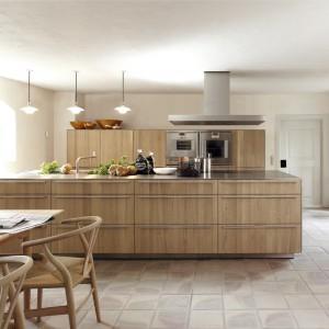 Bardzo nowoczesna kuchnia ekskluzywnej niemieckiej marki Bulthaup. Duża, długa wyspa stanowi jedyną powierzchnię roboczą, a przechowywać można w jej licznych szufladach i w towarzyszącej jej wysokiej zabudowie. Najlepszy dowód na to, że drewno wygląda pięknie również w nowoczesnej formie. Fot. Bulthaup.