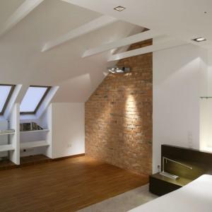 W jasnej, przestronnej sypialni na poddaszu największą dekoracją są belki stropowe oraz duża ilość skosów. Aby je wyeksponować część ściany wyłożono czerwoną cegłą. Projekt: Piotr Gierałtowski. Fot. Bartosz Jarosz.