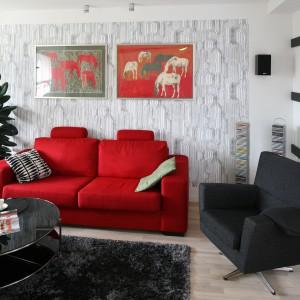 Klimat tego salonu to zasługa świetnie skomponowanych kolorów – mocnych i wyrazistych, dalekich od monotonii, ale i przytulnych. To właśnie dzięki nim proste, spokojne wnętrze pozbawione jest nudy, a każdy jego metr przepełnia pozytywna energia. Czerwona kanapa doskonale prezentuje się na tle ściany wykończonej tapetą, na której dumnie prezentują się oryginalne obrazy Agnieszki Kruk. Projekt: Marta Kruk. Fot. Bartosz Jarosz.
