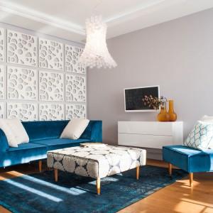 Pokój dzienny skomponowano z bieli oraz różnych odcieni niebieskiego. Turkusowe meble wypoczynkowe doskonale prezentują się na tle wyłożonej ażurowymi panelami ściany. Projekt: Arkadiusz Grzędzicki. Fot. Adam Ościłowski, panadam.pl.