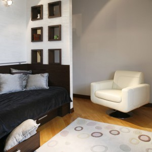 Biały fotel w skórzanym obiciu podkreśla stylowy charakter wnętrza, jak również jest bardzo przydatny podczas odwiedzin kolegów. Projekt: Julita Chrząstek. Fot. Monika Filipiuk-Obałek.