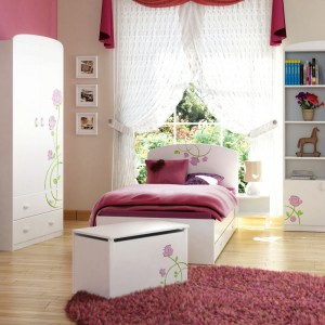 Białe łóżko dla dziewczynki przełamane szczyptą koloru w formie atrakcyjnych, przyciągających wzrok grawerów. Pnące się po wezgłowiu pędy urzekają naturalnością i niezaprzeczalnym wdziękiem. Kolekcja: Róża Róż marki Mablik. Cena: od 890 zł. Fot. Meblik.
