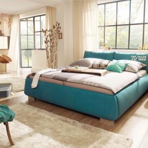 Jeśli znudziła ci się beżowa sypialnia, ożyw ją kolorem. Zamiast barwnych dodatków proponujemy jednak postawić na mebel, np. łóżko tapicerowane zieloną tkaniną. Fot. Tom Tailor.