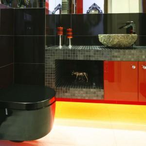 Elegancką łazienkę z nieco orientalnymi nawiązaniami ożywia intensywny akcent w postaci czerwonych frontów do zabudowy umywalki oraz oryginalne żółte podświetlenie. Projekt: Jolanta Kwilman. Fot. Bartosz. Jarosz.