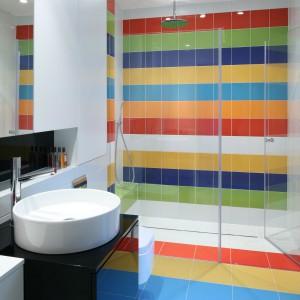 Młodzieżowa łazienka jest niezwykle kolorowa. Podłoga przechodzi od żółci, po zieleń, błękit i kolejne żywe kolory. Wnęka prysznicowa jest wręcz skąpana w żywych barwach. Projekt: Katarzyna Kiełek, Agnieszka Komorowska-Różycka. Fot. Bartosz Jarosz.