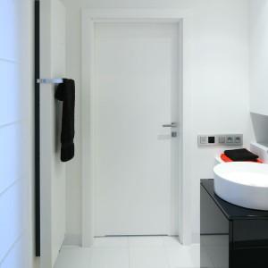 Strefa wejściowa tej łazienki została wykończona w bieli. Dopiero przy umywalce wkracza tutaj kolor, który rozpościera się dalej feerią barw. Projekt: Katarzyna Kiełek, Agnieszka Komorowska-Różycka. Fot. Bartosz Jarosz.
