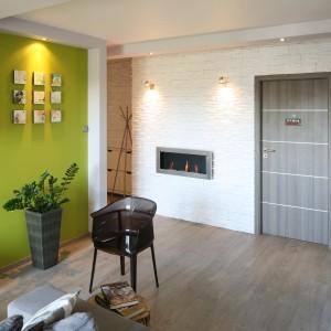 W niewielkim mieszkaniu przedpokój całkowicie zintegrowano ze strefą dzienną, rezygnując ze wszelkich ścian działowych oraz nadając jej salonowy charakter. Projekt: Arkadiusz Grzędzicki. Fot. Bartosz Jarosz.