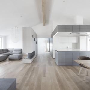 Przestronna część dzienna mieści w sobie ultra-nowoczesną kuchnię, jadalnię oraz strefę wypoczynku. Salon oddziela od kuchni niewielka półścianka działowa o asymetrycznej, geometrycznej formie. Projekt: Destilat Design Studio. Fot. Monika Nguyen.