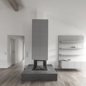 Asymetryczne eternitowe płyty posłużyły również za materiał wykończeniowy zabudowy kominka. Zastosowane na wielu płaszczyznach w obrębie całego mieszkania, są jego wspólnym mianownikiem. Projekt: Destilat Design Studio. Fot. Monika Nguyen.