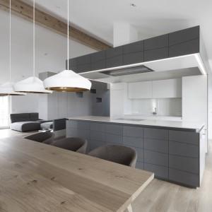 Kuchnię otwarto na dużą jadalnię dla ośmiu osób. Stół wykonano z drewna, harmonizującego odcieniem z podłogą. Wzornictwo stołu jest bardzo proste, wręcz minimalistyczne, wpisujące się tym samym w estetykę całego wnętrza. Projekt: Destilat Design Studio. Fot. Monika Nguyen.