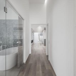 Do salonu kąpielowego prowadzą przeszklone drzwiczki. Jeśli właścicielom zależy na większej intymności, mogą je przesłonić zawieszoną w drzwiach tkaniną. Projekt: Destilat Design Studio. Fot. Monika Nguyen.