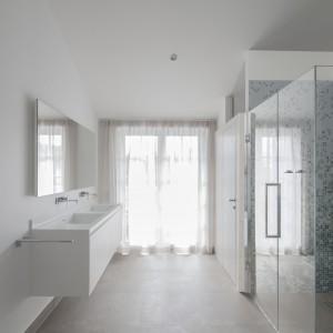 Pozostałe pomieszczenia usytuowano wokół serca mieszkania, jakim jest strefa dzienna. Duża łazienka małżeńska została połączona z master bedroom dla pana i pani domu. Projekt: Destilat Design Studio. Fot. Monika Nguyen.