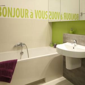 Soczysta zieleń świetnie ożywia wystój małej łazienki, który został oparty na bieli, beżach i szarości. Fioletowe dodatki doskonale uzupełniają aranżację. Projekt: Marta Kruk. Fot. Bartosz Jarosz.