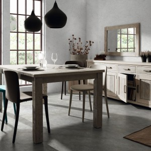 Prosty, tradycyjny stół drewniany w nieco przygaszonej, bardzo modnej w tym sezonie, barwie drewna. Towarzyszą mu komoda w korespondującym kolorze oraz różnobarwne krzesła. Całość aranżacji utrzymano w kolorach ziemi, które są bardzo na topie. Fot. LePukka.