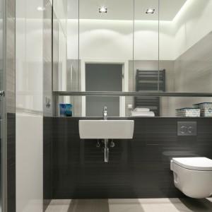 Szarość nada łazience modny, minimalistyczny wygląd, nie przytłaczając przy tym niewielkiego wnętrza. W połączeniu z bielą i dużą ilością luster będzie wyglądać bardzo efektownie. Projekt: Anna Maria Sokołowska mieszkanie. Fot. Bartosz Jarosz.