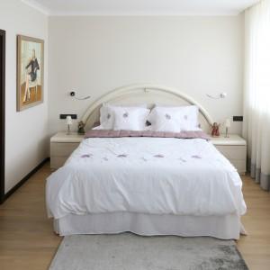 Eleganckie łóżko z owalnym wezgłowiem sprawia, że aranżacja zyskuje kobiecy charakter. Efekt wzmacnia pościel w subtelne kwiaty oraz lekkie firanki zdobiące duże okna. Projekt: Izabella Korol. Fot. Bartosz Jarosz.
