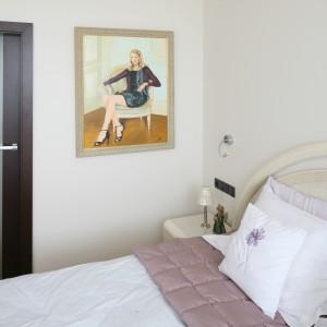 Jednolite ściany w kolorze jasnego beżu nadają wnętrzu spokojny wygląd. Jedyną dekoracją jest nowoczesny portret zawieszony przy drzwiach. Projekt: Izabella Korol. Fot. Bartosz Jarosz.