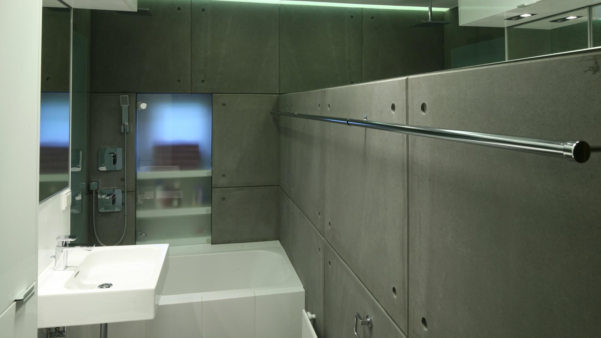 Główne skrzypce gra w tej łazience beton, którym wykończone są zarówno ściany,  jak i podłoga. To on nadaje wnętrzu surowy, minimalistyczny charakter. Szare betonowe płyty o gładkiej powierzchni stworzyły harmonijny zestaw z bielą, szklanymi taflami oraz elementami ze stali nierdzewnej. Projekt: Marcin Lewandowicz. Fot. Bartosz Jarosz.