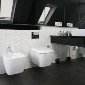 W tym wnętrzu biel i czerń zróżnicowano za pomocą faktur. W łazience znajdziemy połyskujące fronty szafek, delikatne mozaiki i gładkie, wielkoformatowe powierzchnie. Projekt: Małgorzata Borzyszkowska. Fot. Bartosz Jarosz.