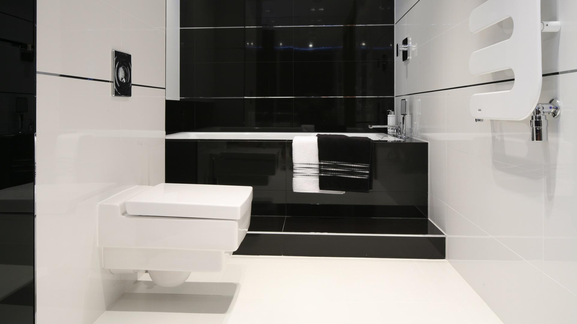 Biel i czerń to pomysł na ponadczasową, elegancką łazienkę. Gładkie, połyskujące powierzchnie przełamano ozdobnymi, poziomymi listwami, które stanowią ciekawy element dekoracyjny. Projekt: Anna Maria Sokołowska. Fot. Bartosz Jarosz.