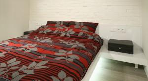 Biała cegła na ścianie, drewno na podłodze i pomysłowe łóżko, które skupia w sobie również funkcje innych mebli. To atrybuty nowoczesnej, funkcjonalnej i oryginalnej sypialni.