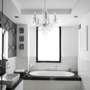 Biel i czerń dodaje wnętrzom elegancji, doskonale sprawdza się we wnętrzach klasycznych. Białe, marmurowe płytki zestawiono z czarnym, granitowym blatem i dekoracyjną tapetą. Projekt: Magdalena Smyk. Fot. Bartosz Jarosz.