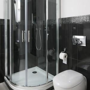 Czarne, połyskujące płytki zastosowano również w strefie kąpieli. Dzięki temu, że zdobią one ścianę jedynie do połowy wnętrze nie wydaje się ciemne i ponure. Biel doskonale jest rozjaśnia. Projekt: Katarzyna Merta-Korzniakow. Fot. Bartosz Jarosz.