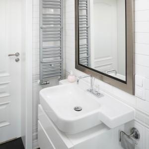 Wąski grzejnik z połyskującą powierzchnią nawiązuje do chromowanych elementów w łazience. Projekt: Iwona Kurkowska. Fot. Bartosz Jarosz.