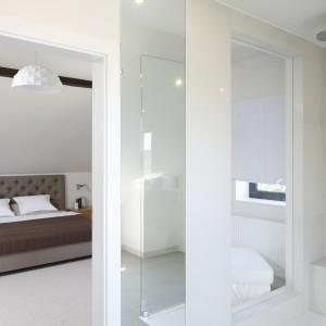 Łazienka znajduje sie obok sypialni. Oba wnętrza stanowią spójną, kolorystyczną całość. Przeszklenie umieszczone w strefie prysznicowej optycznie łączy obie przestrzenie. Fot. Bartosz Jarosz.