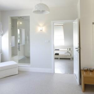 Sypialnię i łazienkę wizualnie połączono za pomocą przeszklenia, które wydziela strefę prysznica. Przeszklona ściana dodatkowo wprowadza do wnętrza światło dzienne.  Fot. Bartosz Jarosz.