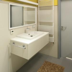 Łazienka jest prosta i nowoczesna. Stonowane wnętrze ożywia jedynie ściana w kolorze żółtym. Grzejnik jest elementem, który subtelnie wpisuje się w aranżację wnętrze. Projekt: Konrad Grodziński. Fot. Bartosz Jarosz.