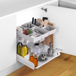 Górny poziom wyposażony jest w kilka plastikowych pojemników z przegródkami. Dolna półka, wykonana w linii Libell, wyposażona jest w uchwyt utrzymujący deskę do krojenia. Fot. Peka.
