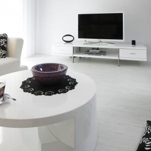 W strefie wypoczynkowej króluje odprężająca biel. Duża, narożna kanapa, mobilny stolik kawowy  oraz niski stolik telewizyjny tworzą minimalistyczny wystrój, podkreślając nowoczesny charakter salonu. Projekt: Joanna Ochota. Fot. Bartosz Jarosz.