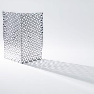 Zaprojektowany dla Glas Italia parawan, wykonany z dwóch warstw szkła, tak ze sobą zestawionych, że przeźroczyste powierzchnie sąsiadują z prostokątnymi niewielkimi lusterkami. Dzięki temu uzyskano efekt ażurowej powierzchni, przepuszczającej światło i rzucającej wzorzysty cień... Fot. Kenichi Sonehara.