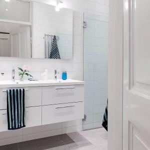 W jasnych łazienkach ważnym elementem są dodatki, które ożywiają przestrzeń: kolorowe dozowniki, wzorzyste ręczniki. Fot. Alvhem Mäkleri.